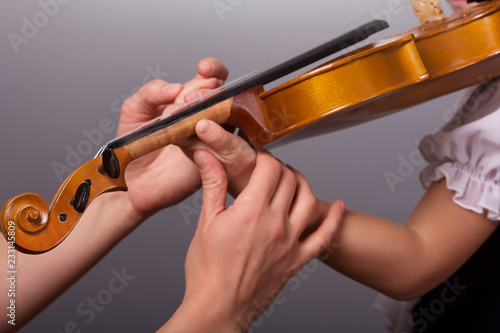 Cuadros en Lienzo Hands of a teacher of playing the violin correct little pupil on gray background
