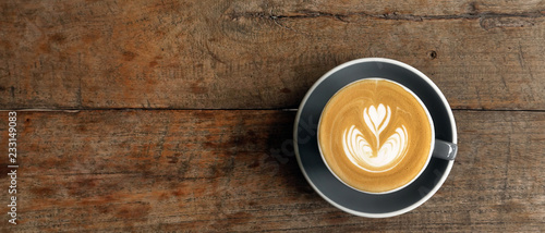 Fotografia a cup of latte art coffee on wooden background