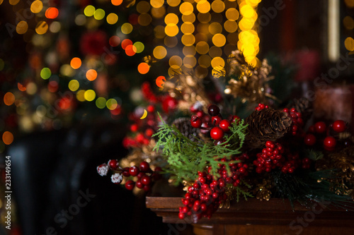 Fototapeta Details of the scenery of the new year. Red berries, Christmas lights, gifts, festive table setting in the light of lights garlands and home decorations. obraz na płótnie