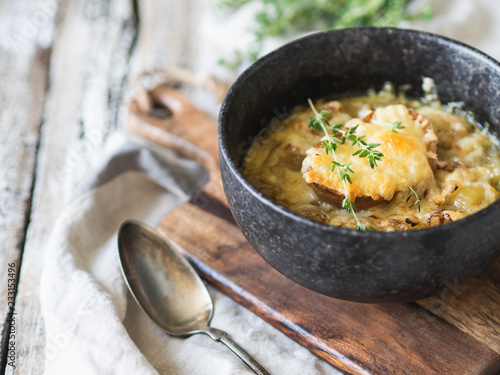 Traditional french onion soup with toast, cheese and fresh thyme in a black bowl on a wooden brown board on a rustic wooden background Fototapete