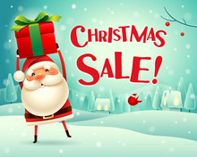 Christmas Sale! Santa Claus Holds Up Gift Present In Christmas Snow Scene Winter Landscape.