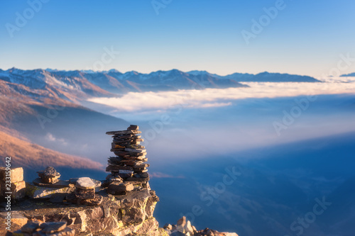Tableau sur Toile Cairn of stone on mountain top with amazing panoramic view of Alps mountain range, clouds and blue sky