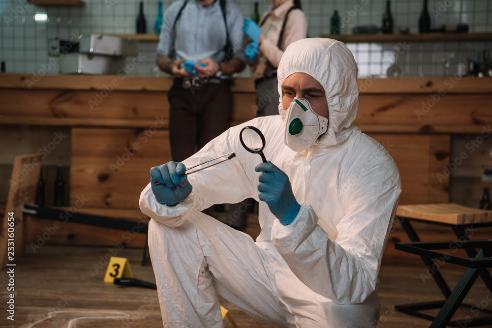 Fototapeta focused forensic investigator examining evidence with magnifying glass at crime scene with colleagues working behind