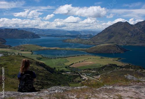 Fotografia  A woman sitting and looking at the Lake Wanaka near the town Wanaka in New Zeala
