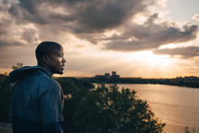 Thoughtful Male Athlete Standing On Hill Against Sky During Sunset