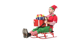 Cheerful Excited Man In Christmas Elf Costume Holding Pile Of Presents And Riding Sleigh Isolated On White
