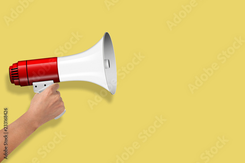 Photo  Hand Hold Megaphone isolated on yellow background