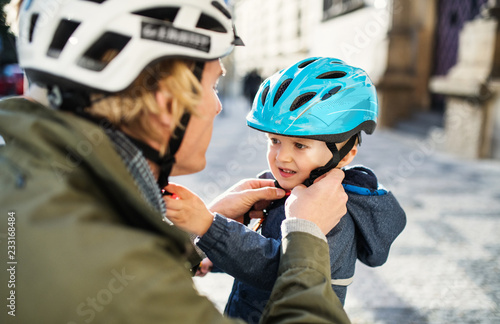 Fototapeta A young father putting on a helmet on his toddler son's head outdoors in city