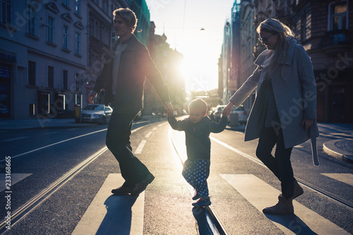 A small toddler boy with parents crossing a road outdoors in city at sunset Fototapeta