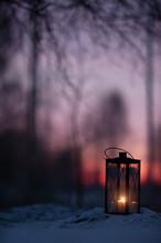 Lantern In Snow Against Defocused Sunset Forest Background.