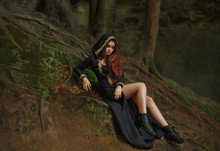 Witch With Red Hair In A Long Black Dress With Open Legs, Hooded Cloak, Leather Boots Stands In The Foggy Forest With Rays Of Moonlight. Pretty Dark Elf From Medieval Ages. Art Photo, Creative Colors