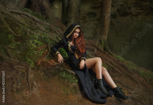 Tableau sur Toile witch with red hair in a long black dress with open legs, hooded cloak, leather boots stands in the foggy forest with rays of moonlight