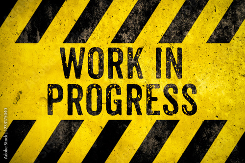 Work in progress warning sign text with yellow and black stripes painted over concrete wall cement texture background. Concept for do not enter the area, caution, danger, construction site.