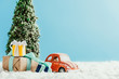 close-up shot of toy red car with presents and christmas tree standing on snow made of cotton on blue background
