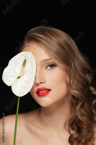 Fotografía  Portrait of young beautiful woman with wavy hair and red lips covering eye with