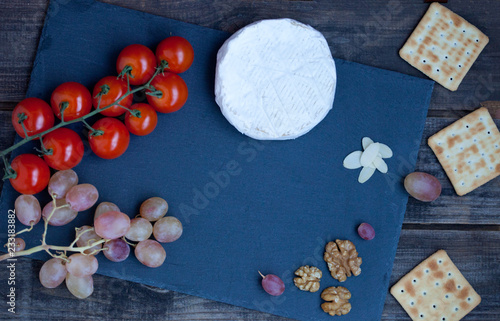 Camembert cheese on a black stone plate with tomatoes, crackers, nuts and grape