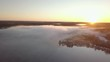 Aerial - Autumn misty morgning in sweden forest. sunrise hitting the trees. big lake in the middle. flying above the fog. 4k