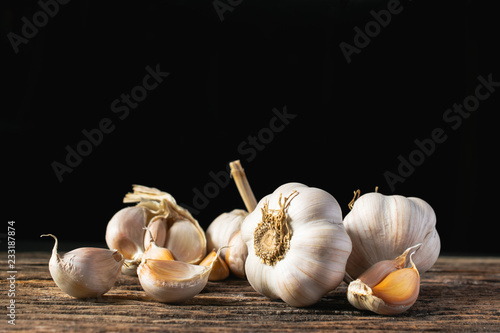 Closeup garlic on wooden texture on for cooking on dark background Wallpaper Mural