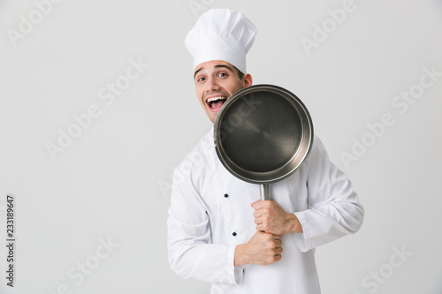 Fototapeta Emotional young man chef indoors isolated over white wall background holding frying pan. obraz