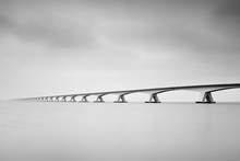 The Zeelandbrug (Zeeland Bridge) In The Dutch Province Of Zeeland, Photographed In Black & White, Long Exposure Shot.