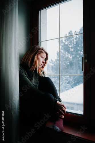 Sad Woman Sitting By The Window Looking Outside Buy This Stock