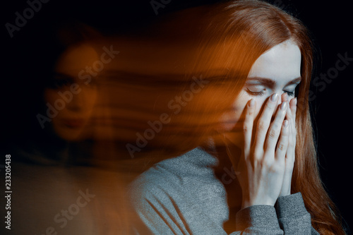 Blurred picture of young beautiful redhead girl with depression covering her mouth