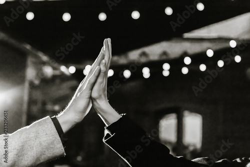 Silhouettes of hands of lovers on a background of blurry lights. - 233206651