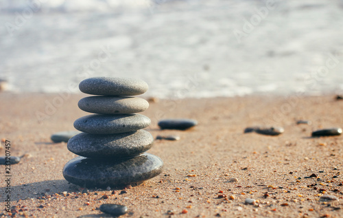 Zen pyramid of spa stones on the blurred sea background. Sand on a beach. Sea shores. Water waves texture. Left side of photo. Place for text.