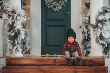 Cute Child Boy Sits On The Porch Of The Magic House Of Santa Claus. Miracle Time. Merry Christmas And Happy New Year
