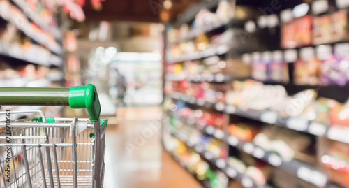 Photo Empty green supermarket shopping cart with abstract blur grocery store aisle def