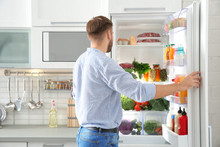 Man Choosing Food From Refrigerator In Kitchen