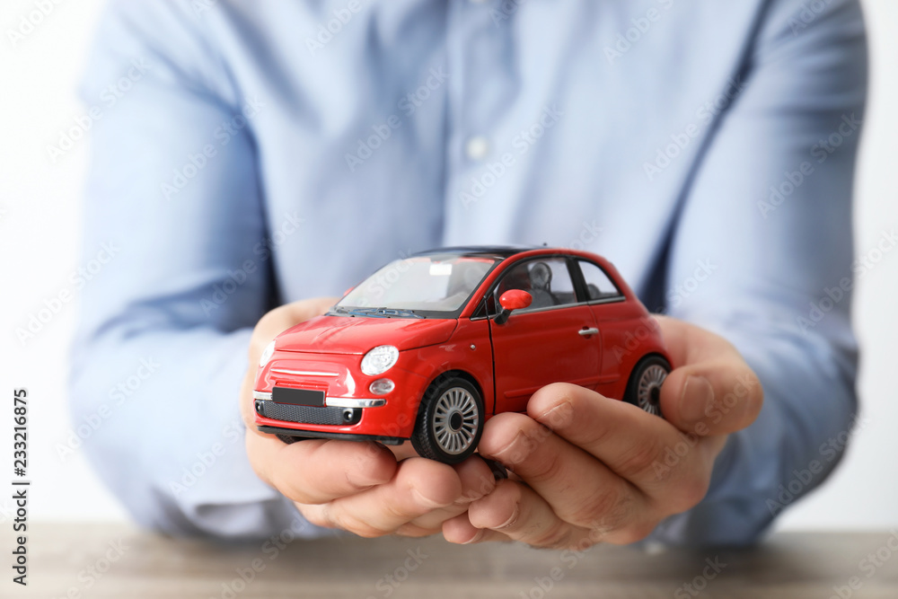 Fototapeta Male insurance agent holding toy car, closeup
