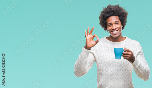 Foto auf AluDibond Kaffee Afro american man drinking cup of coffee over isolated background doing ok sign with fingers, excellent symbol