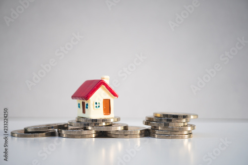 Fototapeta Miniature colorful house on stack coins using as property and financial concept obraz