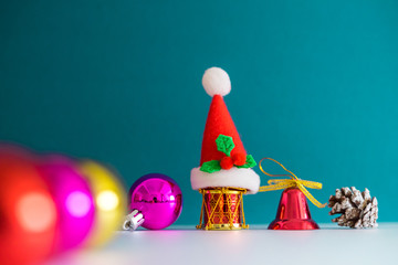 Christmas Concept with copy space.Small Santa Claus hat with ornament balls,bell,pineconse and small present.