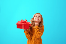 Portrait Of A Little Girl In A Warm Mustard Knitted Sweater On A Cyan Background. The Child Looks Dreamily Up And Holds A Red Box With A Gift. The Concept Of Celebration, Giving And Receiving A Gift