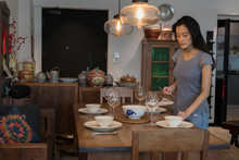 Young Singaporean Woman Getting The Dinner Table Ready