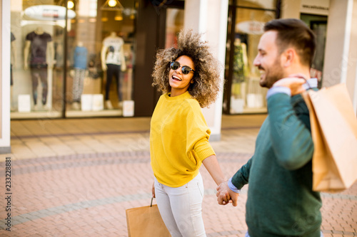 Fotografía  Young multiethnic couple with bags in the shopping