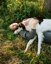 Woman And Dog Lying On Grass