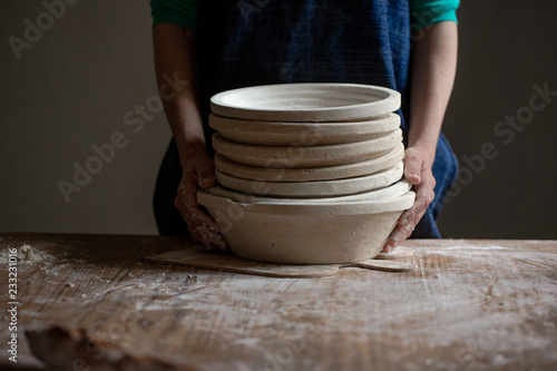 A baker holds baskets to ferment the bread