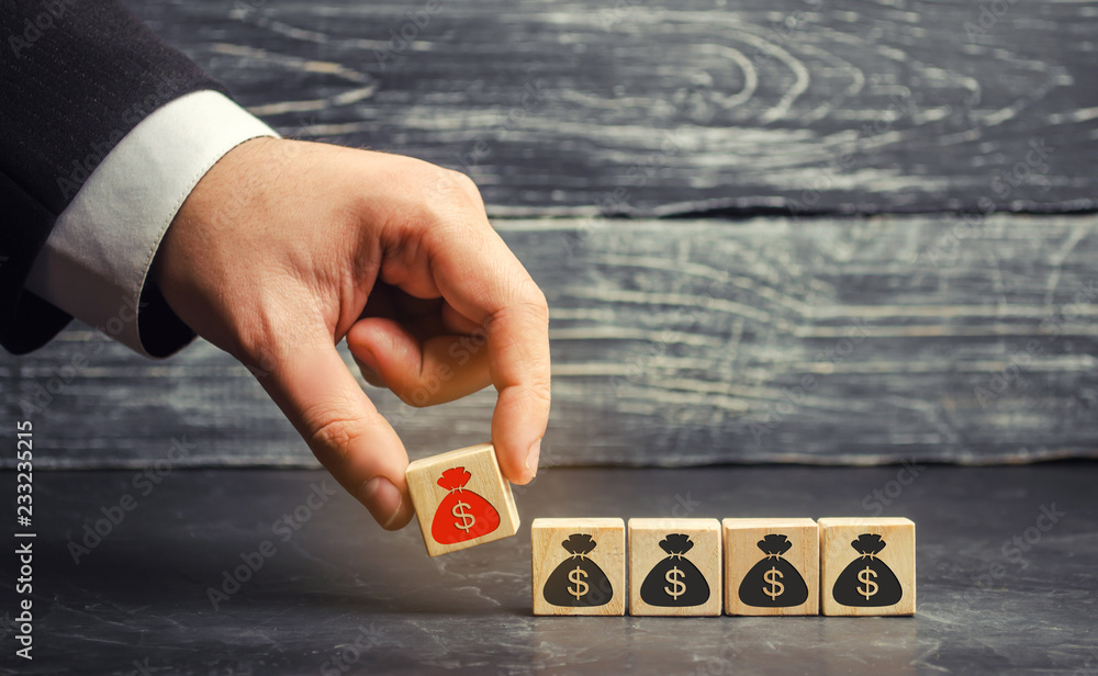 Fototapety, obrazy: businessman removes a cube with a picture of dollars. financial and economic crisis. capital outflow. sabotage of the economy. bankruptcy. pressure on small businesses. falling prices. cash loss