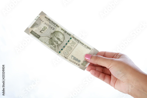 Fotografering  Hand holding 500 rupee notes against white background