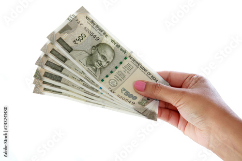 Fotografiet  Hand holding 500 rupee notes against white background
