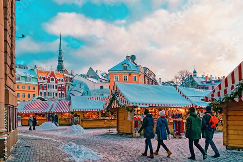 Foto op Plexiglas Kerstmis People stroll down aisle at Christmas Market at Riga