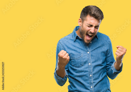 Fotografiet  Young handsome man over isolated background very happy and excited doing winner gesture with arms raised, smiling and screaming for success