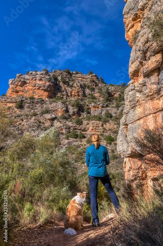 Blonde woman with her blonde border collie mix dog stopped along a trail in a canyon looking up at the orange, brown and green canyon walls and the bright blue sky Fototapet