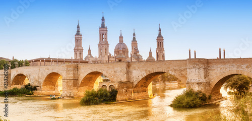 Basilica Cathedral of Our Lady of Pillar and bridge over Ebro River at sunset in Zaragoza, Aragon, Spain. Famous tourist landmark