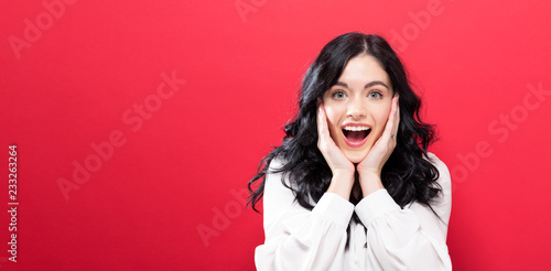 Photographie  Surprised and excited young woman posing on a solid background