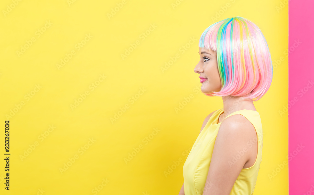 Fototapety, obrazy: Beautiful woman in a bright colorful wig on a split yellow and pink background