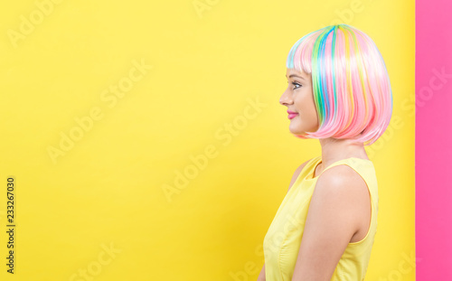 Fotografie, Obraz  Beautiful woman in a bright colorful wig on a split yellow and pink background